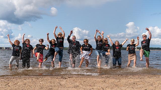Etelä-Karjalan liiton henkilökuntaa kirmaa iloisina rantavedessä kauniina kesäpäivänä.