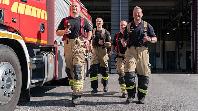 Neljä palomiestä juoksee työasuissaan paloauton vierellä.