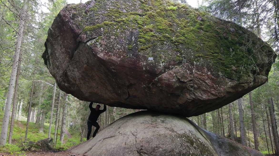Suuri siirtolohkare, joka on maata vasten vain pieneltä kulmaltaan. Kiven alla on mies, joka näyttää ikään kuin pitelevän lohkaretta ilmassa.