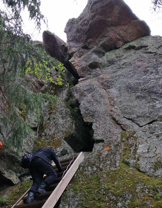 Ihminen kiipeää tikkaita pitkin ylhäällä olevaan kallioluolaan.