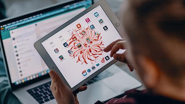 Mies katsoo tablettia. Takana on tietokoneen näyttö.
