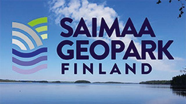 Saimaa Geoparkin logo ja sen takana kaunis kesäinen järvimaisema.